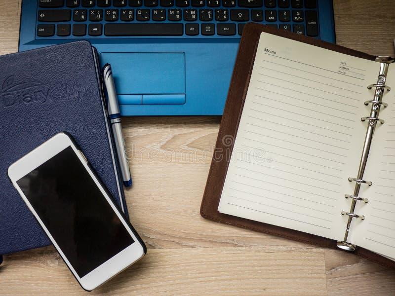 Lieu de travail de bureau avec l'ordinateur portable, le carnet, le téléphone et le stylo sur la table en bois images libres de droits