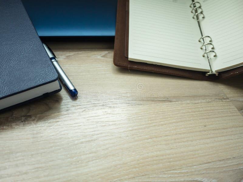Lieu de travail de bureau avec l'ordinateur portable, le carnet, le téléphone et le stylo sur la table en bois photos libres de droits