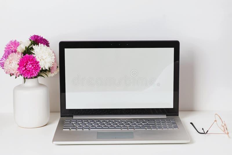 Lieu de travail féminin avec l'ordinateur portable avec l'écran et les fleurs vides blancs dans le vase photo stock