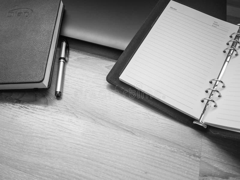 Lieu de travail noir et blanc, de bureau avec l'ordinateur portable, carnet, téléphone et stylo sur la table en bois photos libres de droits