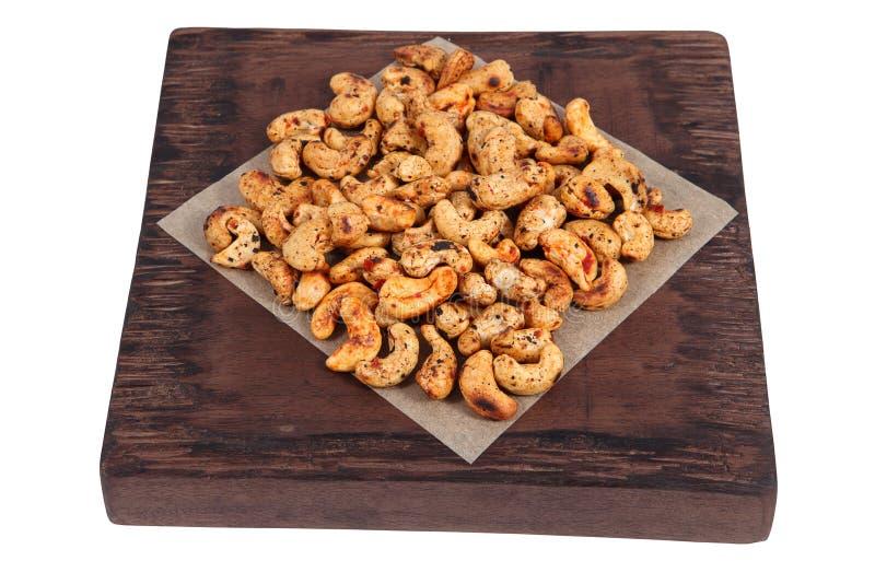 Liez les épices de noix de cajou de rôti sur le panneau de portion de brun foncé images libres de droits