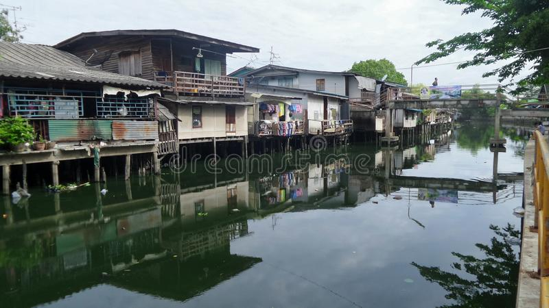 Daily life activity in Small houses on canal bank in the city. Canal front life community in busy city in Thailand . Thais people usually built their homes along royalty free stock image