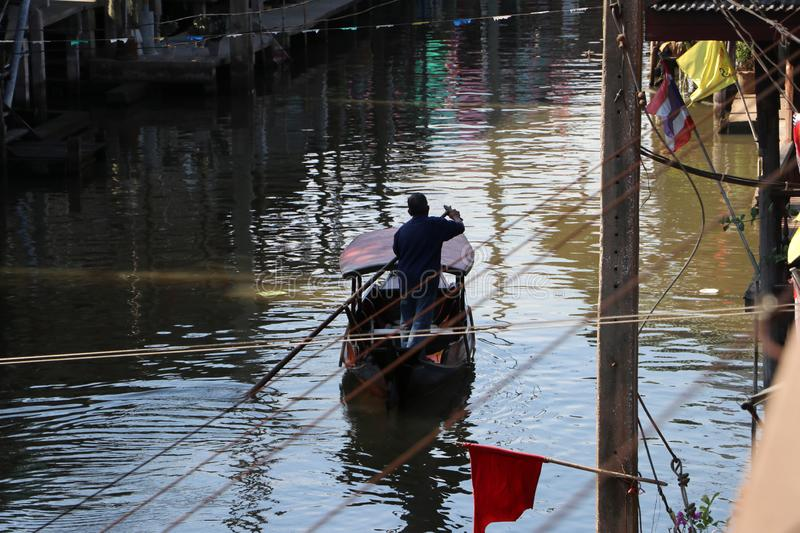 Life along the canal and boatman rowing the Thai traditional small rowboat on the canal. At Damnoensaduak Thailand stock photography