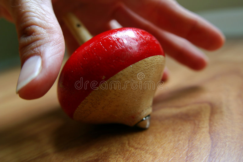 Life is a balancing act. Closeup of a hand reaching for a wooden top stock photos