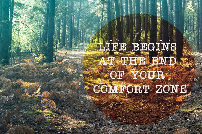 Life begins out. Life begins at the end of your comfort zone written on forest pathway landscape stock photo
