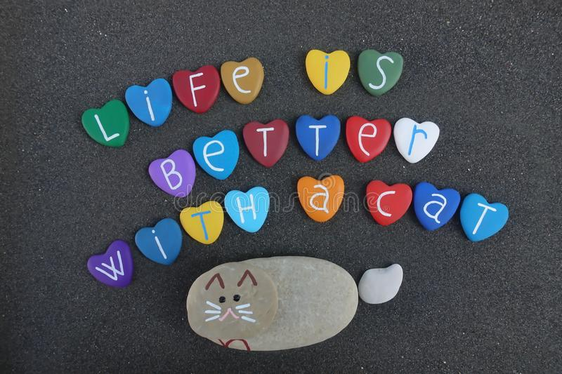 Life is better with a cat, stones art composition on black sand royalty free stock photos
