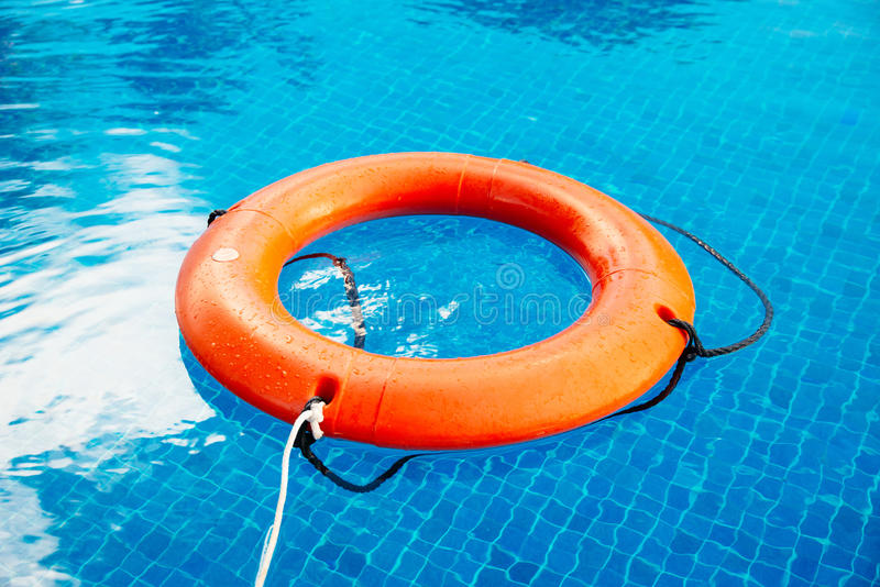 Life buoy afloat in a pool in Mexico. Life buoy afloat in a pool with blue clear water stock photography
