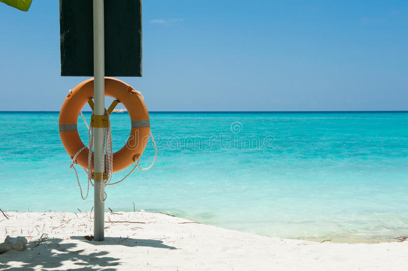 Life buoy attached to a wooden post at the beach in Maldives isl royalty free stock image