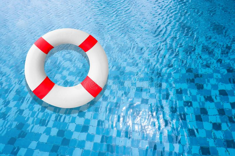 Life Buoy in a Clear Pool Water. Life Belt or Life Preserver Floating on Top of Sunny Blue Water. Safety Equipment, Blue and White stock photo