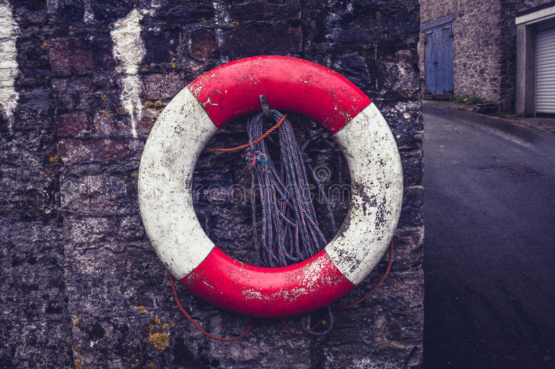 Life buoy on old stone wall. Life buoy hanging from an on old stone wall in harbor town royalty free stock image