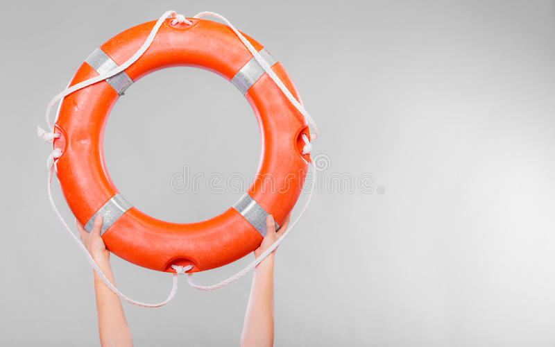 Life buoy ring in female hands. Accident prevention and water rescue. Life buoy ring lifebelt in female hands studio shot gray background royalty free stock image