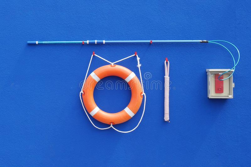 Life buoy ring and rope on a blue wall stock photography