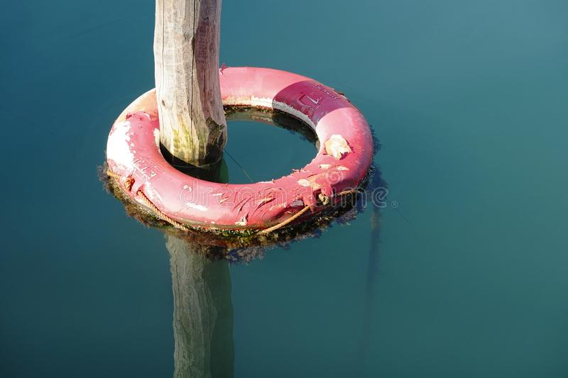 Lifebelt. Life buoy in water anchored to the dock royalty free stock photos