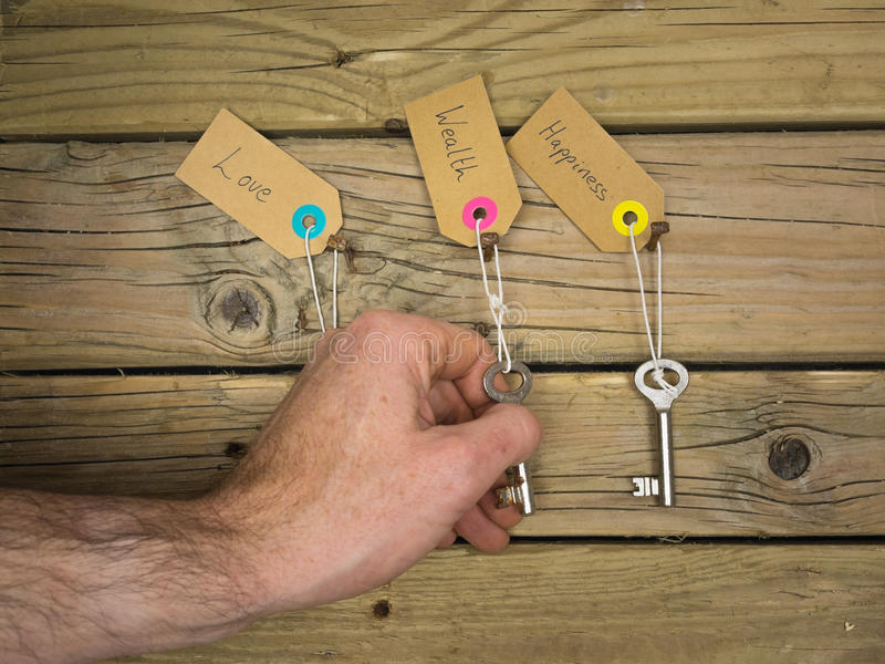 Life choices concept. Old keys hanging on rusty nails against wooden background with labels love, wealth and happiness and a mans hand choosing the key to stock photos