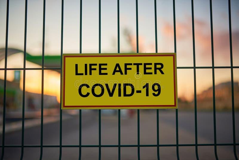 Life After COVID-19 assina uma cerca com vista de cidade azul sobre um fundo no pôr do sol fotos de stock royalty free