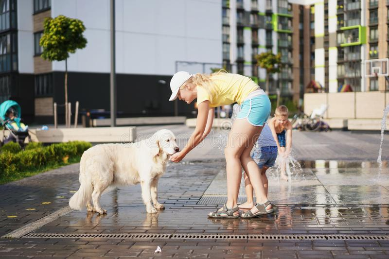 Life with domestic pets in the city - young woman watering a dog with water from a fountain stock photography