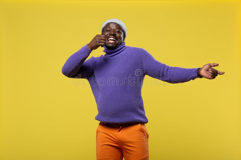 Handsome male person demonstrating his sincere smile. Life enjoyment. Kind young man expressing positivity while standing over yellow background stock image
