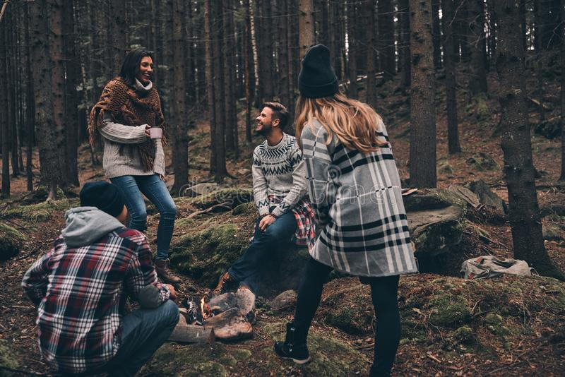 Life filled with friendship. Group of happy young people standing around the campfire while hiking in the woods royalty free stock image