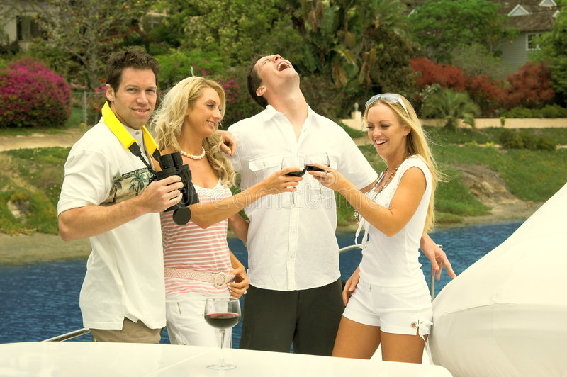 Life Is Good. A group of two men and two women celebrating life with a toast and boisterious laughter during a yacht party
