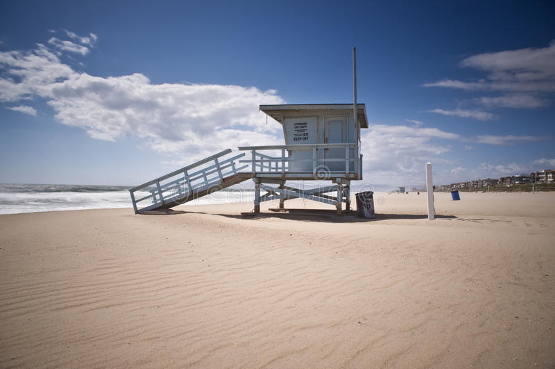 Life Guard Tower on Windy Afternoon. Empty life guard tower in Manhattan Beach on north side of pier. The Strand and its multi-million dollar houses are in the royalty free stock photo
