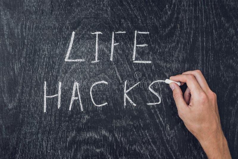 Life hacks written on the blackboard using chalk stock photos