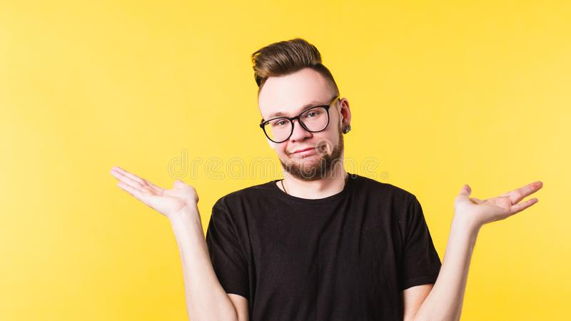 Life happens millennial guy portrait copy space. Life happens. Portrait of confused millennial guy shrugging shoulders helplessly. Indifferent facial expression stock photography