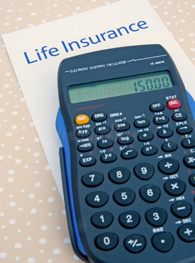 Life insurance; calculating the annual premium. A macro image of the text 'Life Insurance' with a calculator emphasizing the statistical functions on the royalty free stock photography