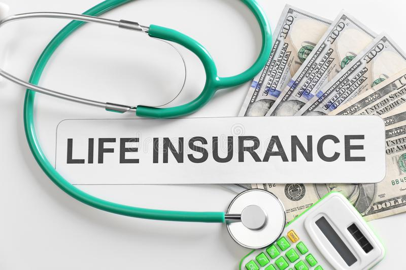 Life insurance concept. Calculator, stethoscope. And banknotes on light background royalty free stock photo
