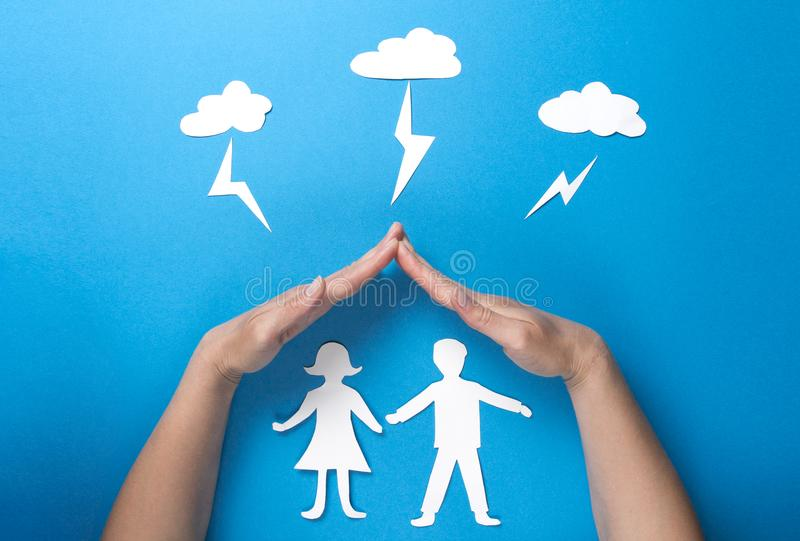 Life insurance and family health concept. Hands protect paper figures origami from lightning from the clouds on blue background stock images