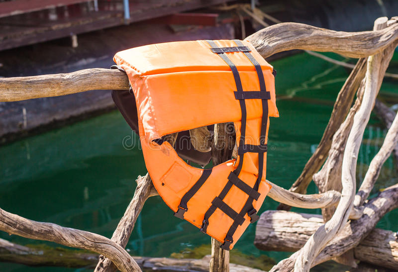 Life jacket in orange colours. Hanging in a fence stock photos