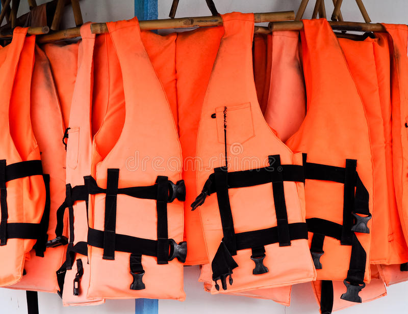 Life jackets. The orange life jackets are hung on the wall royalty free stock photo