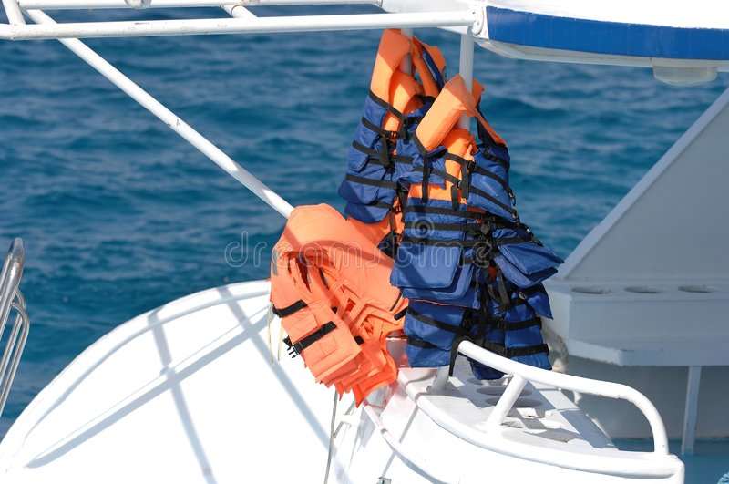 Life jackets on boat. A view of several orange and blue life jackets hung out to dry on the aft deck of a yacht or large motor boat stock images