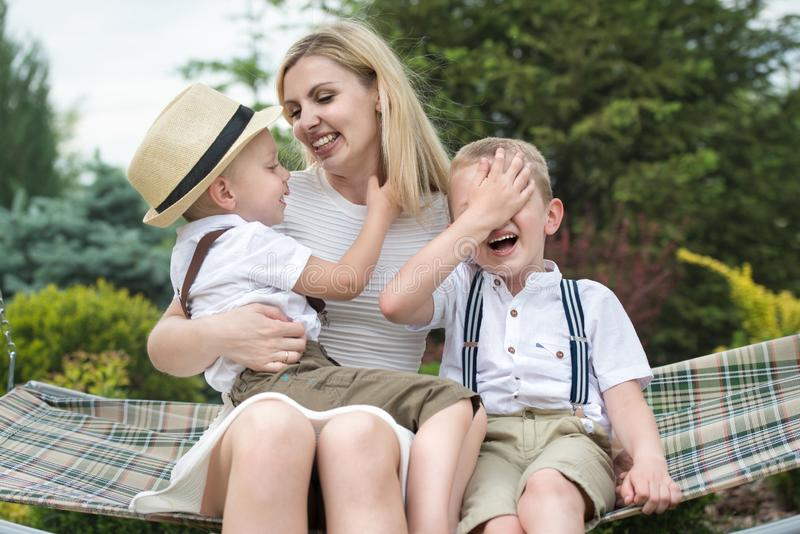 Life moment of happy family!Young mother and two beautiful sons ride on the swings royalty free stock photos