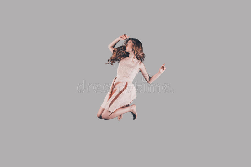 Life in motion. Studio shot of attractive young woman hovering in air stock photography