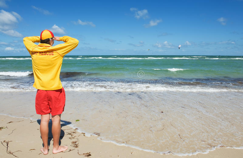 Life saver. Young man life saver watching the situation on the sea stock photography