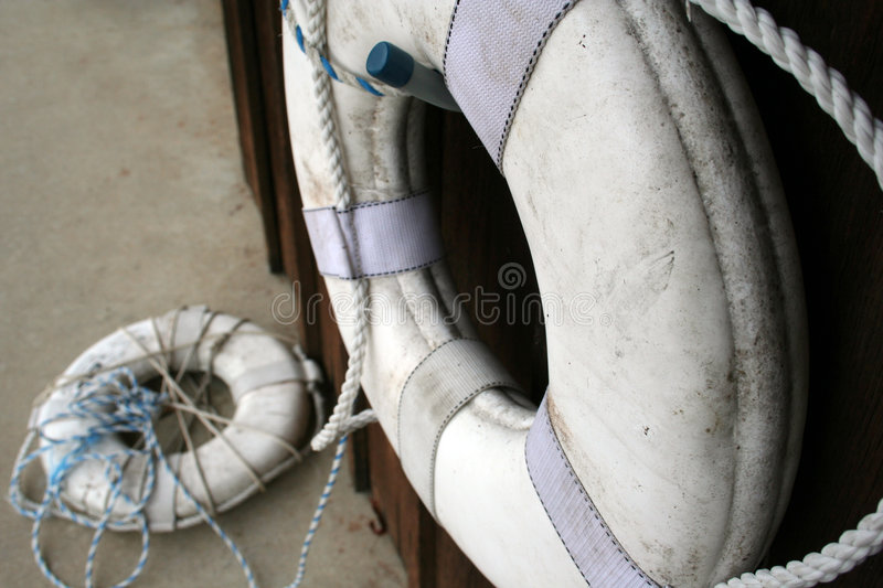 Life Savers. Live Savers on wall and ground by boat house royalty free stock images
