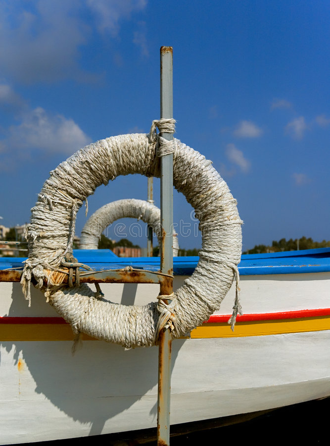 Life savers. Wrapped in ropes near fishermen's boats stock images