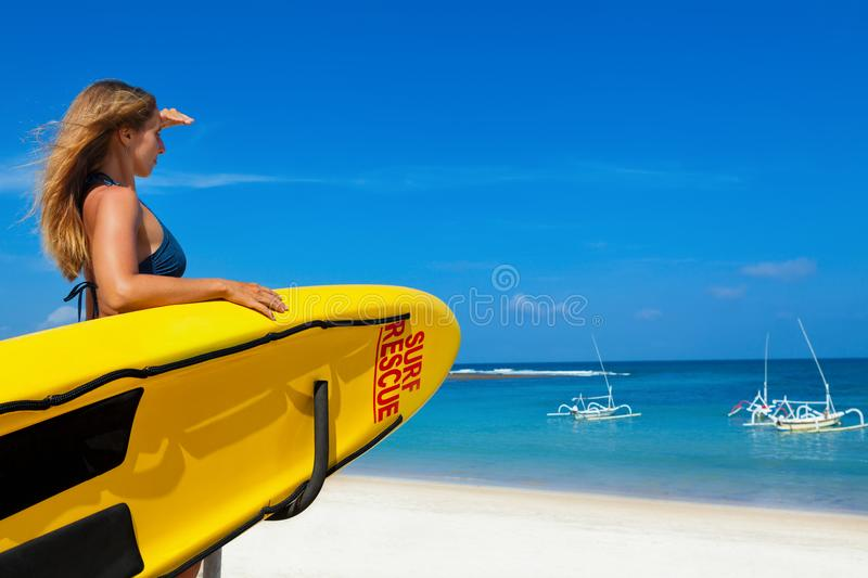 Lifeguard woman stand with surf rescue board on beach stock photo