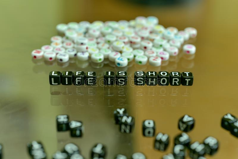 LIFE IS SHORT  written with Acrylic Black cube with white Alphabet Beads on the Glass Background.  stock photos