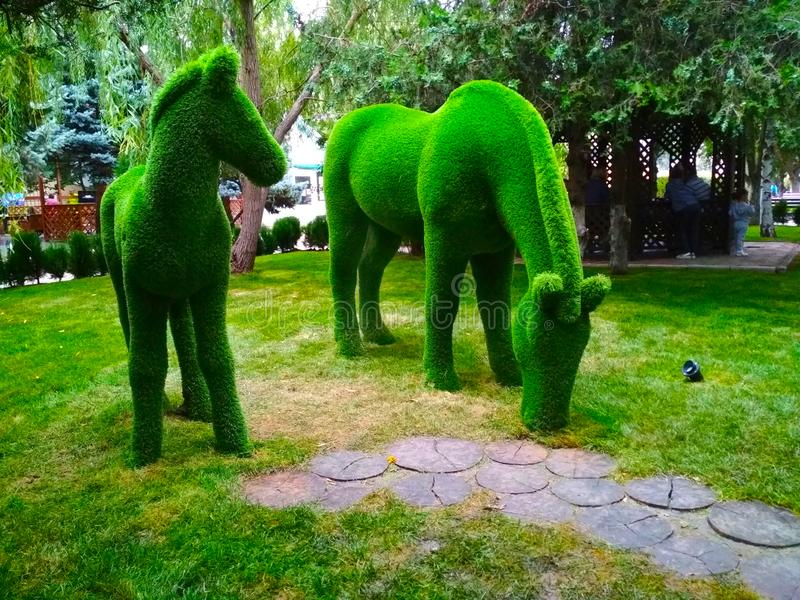 Sculpture of two horses from artificial grass on the background of trees. Life-size sculpture of green horses in the Park stock images