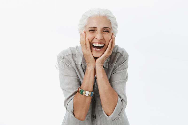 Life only starts when get older. Portrait of charming happy and carefree european senior woman with grey hair laughing royalty free stock photography