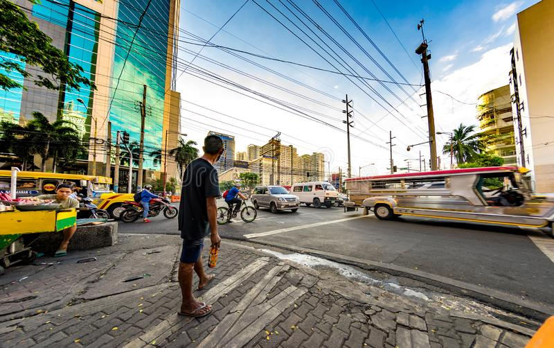 Daily life on the streets of Manila. MANILA, PHILIPPINES - CIRCA MARCH 2018: View on daily life on the streets of the city as cars and pedestrians pass by during royalty free stock image