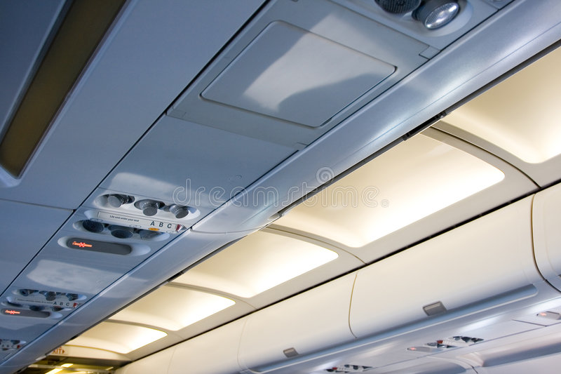 Life vest under your seat 4. Ceiling of airplane showing reading and warning lights royalty free stock photo