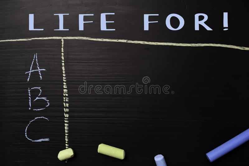Life For! written with color chalk. Supported by an additional services. Blackboard concept stock images