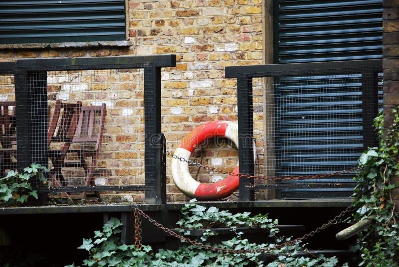 Lifebelt against a brick wall on a balcony. A lifebelt leans against a brick wall on an old wooden balcony stock photography