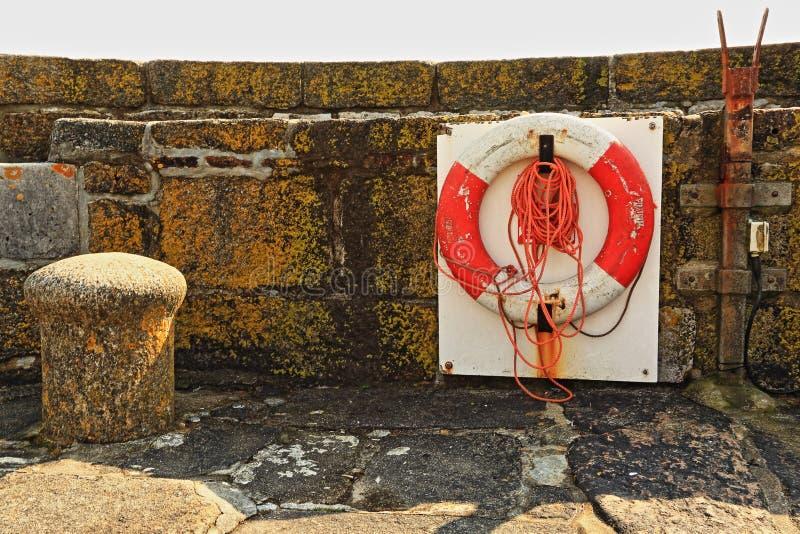 Lifebelt and harbour wall, Charlestown, Cornwall. Lifebelt attached to lichen covered harbour wall at Charlestown, Cornwall stock photography