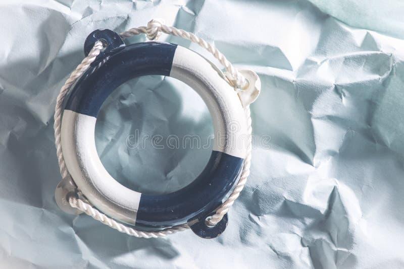 Lifebelt on blue background. Lifebelt on blue paper background royalty free stock photo