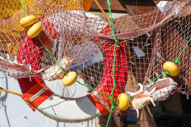 Lifebelt, fishing net, shells. Lifebelt in fishing net with shells above the entrance in the shop stock image