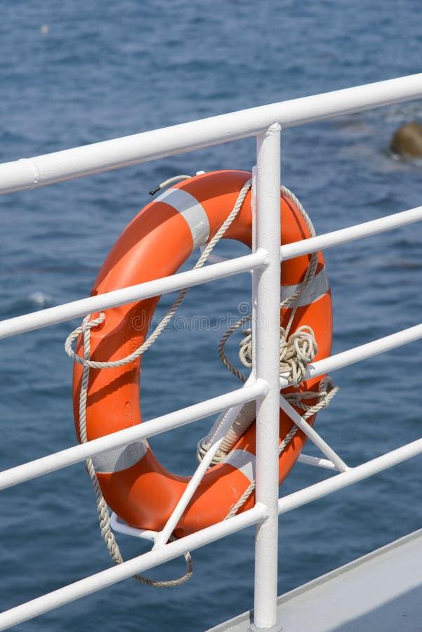 Lifebelt hang on a banister a passenger ship. Orange colored lifebelt and rope hang on a white banister a passenger ship stock photo