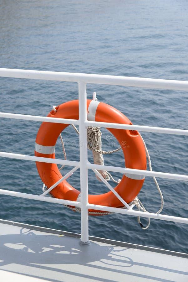 Lifebelt hang on a banister a passenger ship. Orange colored lifebelt and rope hang on a white banister a passenger ship stock photos